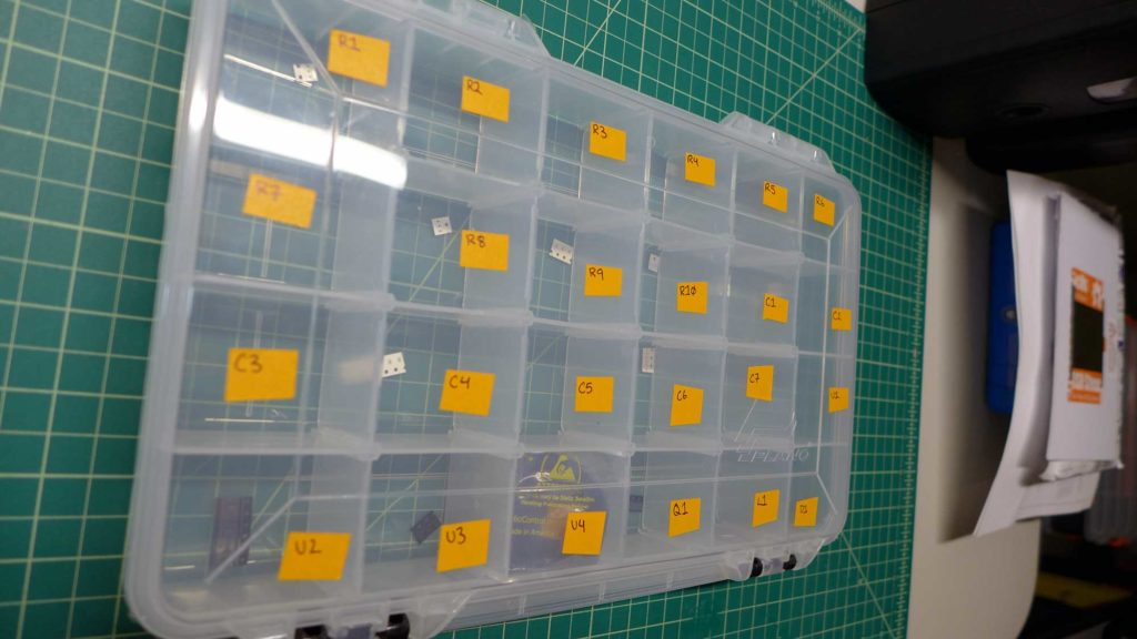 SMT components organized in a plastic container.